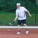 Senior man playing tennis. On a gravel court Stock Photography