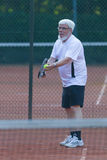Senior man playing tennis. On a gravel court Stock Photos