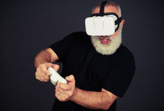 Senior man is playing in virtual reality Stock Photo