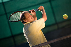 Senior man plays tennis. Active senior man in his 70s playing tennis royalty free stock photography