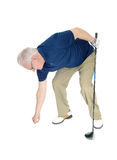 Senior man pleasing his golf ball. A seventy old senior standing with his blue t-shirt, holding his iron in Stock Photo