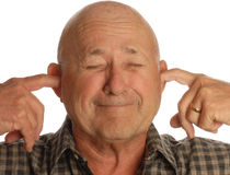 Senior man plugging ears. Bald senior man plugging his ears isolated on white background Stock Photos