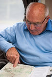 Senior man pointing on map location. Senior man looking at a road map and pointing at a route Royalty Free Stock Photo