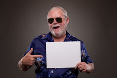 Senior man pointing at a placard Stock Images