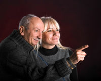 Senior man pointing at something to young woman Stock Image