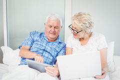 Senior man pointing at tablet with wife Stock Photos