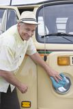 Senior Man Polishes Headlights On His Campervan Stock Photo