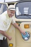 Senior Man Polishes Headlights On His Campervan Stock Photo