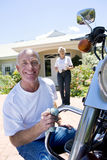 Senior man polishing motorbike on driveway, crouching down, senior woman serving drinks on background, smiling, portrait Royalty Free Stock Photography