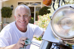 Senior man polishing motorbike on driveway, crouching down, smiling, close-up, portrait Royalty Free Stock Image