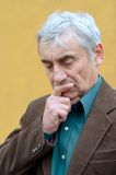 Senior man pondering. Concerned caucasian senior man with his hand on his chin pondering, frowning, looking down. Head and shoulders portrait. Brown corduroy Stock Image
