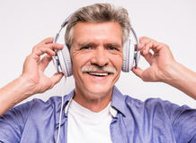 Senior man. Portrait of senior man in headphones listening to music and relaxing on grey background stock photos