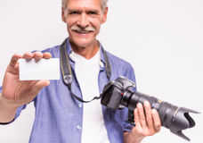 Senior man. Portrait of senior man is holding camera and stretching out business card while standing against grey background royalty free stock photos