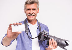 Senior man. Portrait of senior man is holding camera and stretching out business card while standing against grey background royalty free stock photo