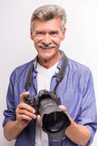 Senior man. Portrait of senior mature man is holding camera while standing against grey background stock photos