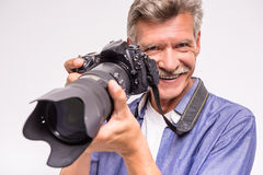 Senior man. Portrait of senior mature man taking a picture while standing against grey background stock photo