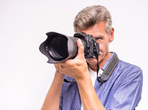 Senior man. Portrait of senior mature man taking a picture while standing against grey background stock images