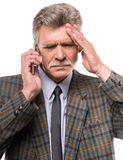 Senior man. Portrait of senior man is suffering from headache, while talking by telephone royalty free stock photography