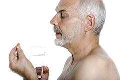 Senior man portrait taking medecine pill Royalty Free Stock Images