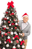 Senior man posing behind a Christmas tree Royalty Free Stock Images