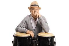 Senior man posing with conga drums stock image