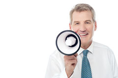 Senior man posing with megaphone. Businessman making announcement over a loudhailer Royalty Free Stock Image