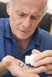 Senior Man Pouring Pills Out Of Bottle Stock Photography