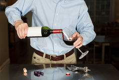 Senior man pouring from wine bottle with blank label. Senior caucasian man standing in kitchen pouring from bottle of red wine with a blank label for copy space Stock Images