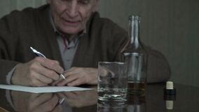 Senior man pours cognac into glass with trembling hands