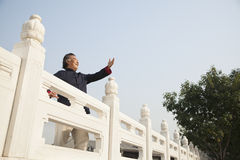 Senior man practicing Taijiquan in Beijing, arms in front Royalty Free Stock Image