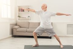 Senior man practicing yoga indoors. Sporty elderly guy practicing yoga indoors. Senior man doing stretching exercise at home. Active lifestyle and healthcare in Royalty Free Stock Images