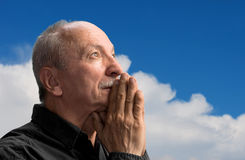 Senior man praying. Agaist blue cloudy sky royalty free stock photos