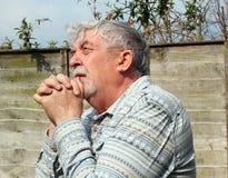 Senior man praying with clasped hands. stock photos