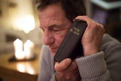 Senior man praying, holding Bible in his hands, eyes closed. Royalty Free Stock Image