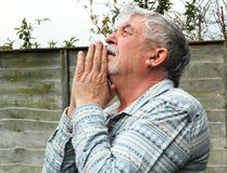Senior man praying. A senior man praying. looking up to heaven with hands together and making a prayer to God stock image