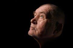 Senior man praying. Old senior man looking up praying in dark royalty free stock photography