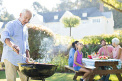 Senior man preparing barbecue while family having meal. In the park royalty free stock images