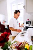 Senior man preparing coffee. Putting sugar in cups. Royalty Free Stock Images