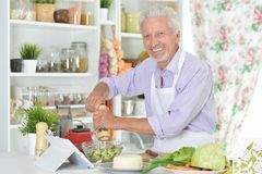Senior man  preparing dinner in kitchen Royalty Free Stock Images