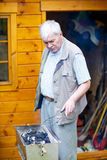 Senior man preparing fire for barbecue, outdoors Stock Images