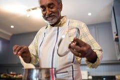 Senior man preparing food at home royalty free stock photo
