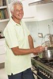 Senior Man Preparing Meal At Cooker Stock Image