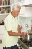 Senior Man Preparing Meal At Cooker Royalty Free Stock Photography