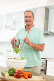Senior Man Preparing Salad In Modern Kitchen Stock Photography