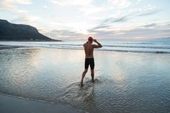 Senior man preparing to swim in the sea at dawn royalty free stock photo