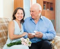 Senior man presenting smiling mature woman jewel. Senior men presenting smiling mature women jewel in box  at home Stock Photos
