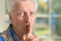 Senior man presses his finger on mouth Stock Photos