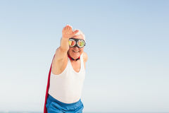 Senior man pretending to be a superhero. On a sunny day Royalty Free Stock Image