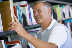 Senior man pulling a library book off shelf.  Stock Image