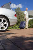 Senior man pulling suitcase on wheels from parked car boot on driveway, smiling, side view, portrait (surface level) Royalty Free Stock Photography